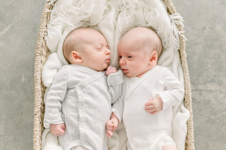 A family of five with newborn twin boys gets family photos done in a bright white studio in Denver Colorado with their older son.