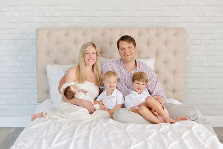 A family fo five getting a newborn portrait in a studio with two boys and the baby is a girl