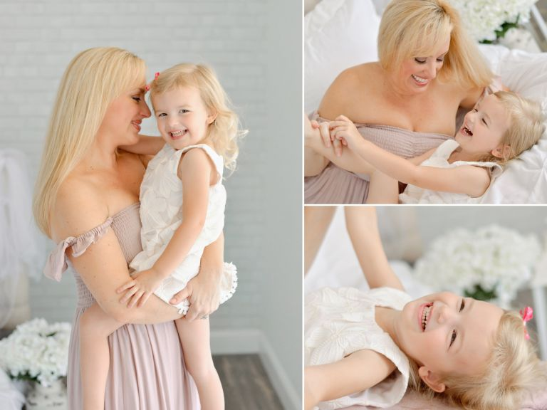 Mom and daughter happily snuggling and giggling on a white bed in a studio for a portrait session
