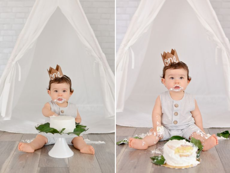 One year old baby boy with dark curls smashes white cake for his first birthday