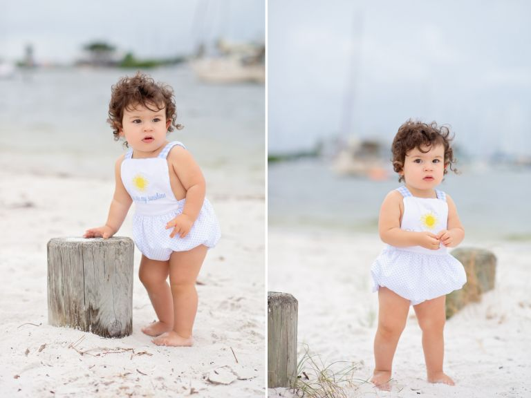 A sweet 18 month old little boy with long dark curls gets his photos taken on an overcast windy day at the beach in Tampa, Florida.