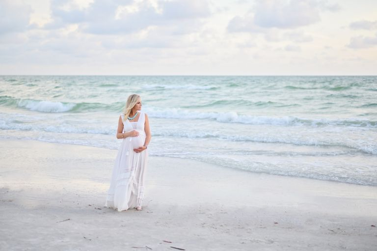 A beautiful blonde family of 3 gets family & maternity photos done on a beach in Redington Shores, FL at sunset time.